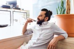 Hombre sonriente con el bollo de la barba y del pelo en la oficina fotografía de archivo