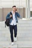Hombre sonriente con el bolso que camina y que habla en el teléfono móvil Imagen de archivo libre de regalías