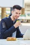 Hombre sonriente con el café y el bocadillo que trabajan en el ordenador portátil Foto de archivo libre de regalías