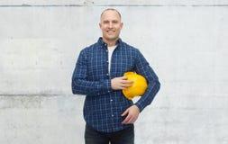 Hombre sonriente con el casco sobre el muro de cemento imagen de archivo libre de regalías
