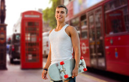 Hombre sonriente con el monopatín en la calle de la ciudad de Londres Foto de archivo