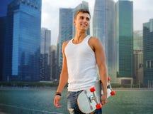 Hombre sonriente con el monopatín sobre la ciudad de Singapur Imagen de archivo libre de regalías