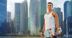 Hombre sonriente con el monopatín sobre la ciudad de Singapur Fotografía de archivo