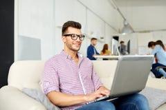 Hombre sonriente con el ordenador portátil que trabaja en la oficina fotografía de archivo
