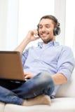 Hombre sonriente con el ordenador portátil y los auriculares en casa Foto de archivo libre de regalías