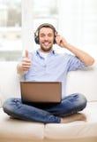 Hombre sonriente con el ordenador portátil y los auriculares en casa Imágenes de archivo libres de regalías