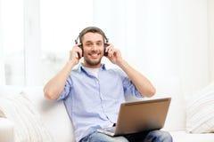 Hombre sonriente con el ordenador portátil y los auriculares en casa Fotos de archivo libres de regalías