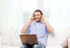 Hombre sonriente con el ordenador portátil y los auriculares en casa Imagenes de archivo