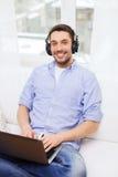 Hombre sonriente con el ordenador portátil y los auriculares en casa Fotos de archivo