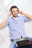 Hombre sonriente con el ordenador portátil y los auriculares en casa Imagen de archivo