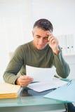 Hombre sonriente con el papel gris de la lectura del pelo Foto de archivo libre de regalías