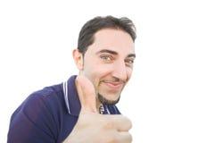 Hombre sonriente con el pulgar para arriba en un fondo blanco. Fotografía de archivo libre de regalías