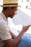 Hombre sonriente con el sombrero que mira el teléfono móvil Imagen de archivo