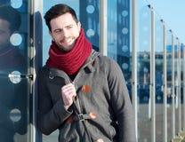 Hombre sonriente con la chaqueta y la bufanda que se relajan al aire libre Imagen de archivo