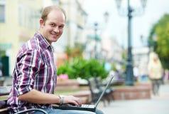 Hombre sonriente con la computadora portátil Imagen de archivo