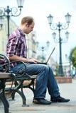 Hombre sonriente con la computadora portátil Imagen de archivo libre de regalías