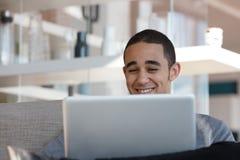 Hombre sonriente con la computadora portátil Fotos de archivo libres de regalías