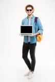 Hombre sonriente con la mochila que coloca y que sostiene el ordenador portátil de la pantalla en blanco Fotos de archivo libres de regalías