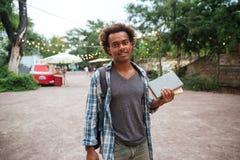 Hombre sonriente con la mochila que coloca y que sostiene los libros al aire libre Imagen de archivo libre de regalías