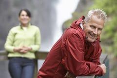 Hombre sonriente con la mujer borrosa contra la cascada fotos de archivo libres de regalías