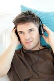 Hombre sonriente con los auriculares que escucha la música imagenes de archivo