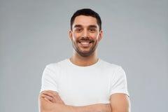 Hombre sonriente con los brazos cruzados sobre fondo gris Fotografía de archivo libre de regalías