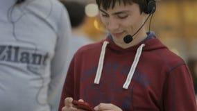 Hombre sonriente con miradas de las auriculares en el smartphone y los textos metrajes