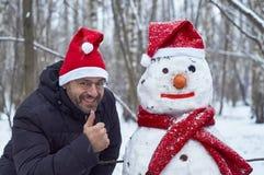 Hombre sonriente con un muñeco de nieve Imagenes de archivo
