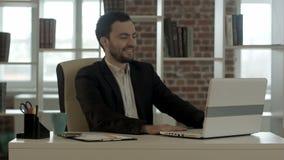 Hombre sonriente con un ordenador portátil en oficina almacen de metraje de vídeo