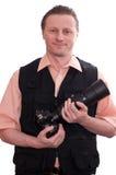 Hombre sonriente con una cámara y una lente enorme Fotos de archivo libres de regalías
