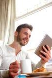 Hombre sonriente de la Edad Media con la tableta y el café fotos de archivo