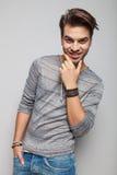 Hombre sonriente de la moda de los jóvenes que fija su barba Fotos de archivo libres de regalías