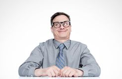 Hombre sonriente emocional difícil astuto en vidrios que piensa la mirada en lado, en fondo ligero foto de archivo libre de regalías