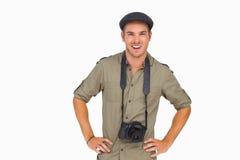 Hombre sonriente en casquillo enarbolado con la cámara alrededor de su cuello Foto de archivo
