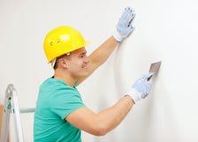 Hombre sonriente en el casco que hace renovaciones en casa Imágenes de archivo libres de regalías