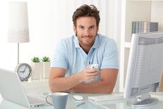 Hombre sonriente en el escritorio con el teléfono móvil Imagen de archivo