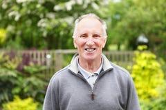Hombre sonriente en jardín imagen de archivo libre de regalías