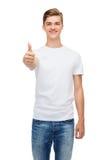Hombre sonriente en la camiseta blanca que muestra los pulgares para arriba Imágenes de archivo libres de regalías