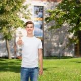 Hombre sonriente en la camiseta blanca que muestra los pulgares para arriba Fotografía de archivo