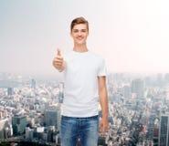 Hombre sonriente en la camiseta blanca que muestra los pulgares para arriba Imagenes de archivo