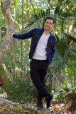 Hombre sonriente en la naturaleza que presenta entre árboles Imagenes de archivo