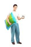 Hombre sonriente en los pijamas que sostienen una almohada y un reloj de alarma Fotografía de archivo