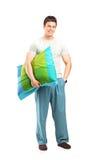 Hombre sonriente en los pijamas que sostienen una almohadilla Imagen de archivo