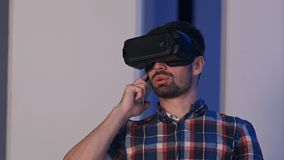 Hombre sonriente en los vidrios de la realidad virtual que tienen conversación sobre el teléfono Imagenes de archivo