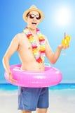 Hombre sonriente en pantalones cortos de la natación, tenencia un cóctel y presentación encendido Foto de archivo libre de regalías