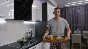 Hombre sonriente en pijamas que camina con la bandeja del desayuno metrajes
