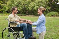 Hombre sonriente en silla de ruedas con el socio que se arrodilla al lado de él Imagen de archivo