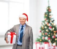 Hombre sonriente en sombrero del traje y del ayudante de santa con el regalo imagen de archivo libre de regalías