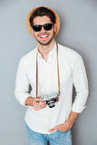Hombre sonriente en sombrero y gafas de sol con la cámara vieja del vintage Imagen de archivo