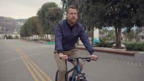 Hombre sonriente en una bici del deporte almacen de metraje de vídeo